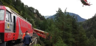 landslide train switzerland, swiss train derails after landslide, train derails in Switzerland, train switzerland alps, A landslide is at the origin of this train derailment in Switzerland. Photo: 20min, train derails in swiss alps august 2014, A train wagon is hanging in trees after a landslide triggered a train derailment between Chur and St-Moritz.