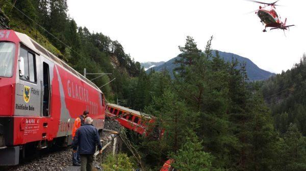 landslide train switzerland, swiss train derails after landslide, train derails in Switzerland, train switzerland alps, A landslide is at the origin of this train derailment in Switzerland. Photo: 20min, train derails in swiss alps august 2014, A train wagon is hanging in trees after a landslide triggered a train derailment between Chur and St-Moritz.