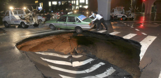 sinkhole, taxi sinkhole, sinkhole swallows taxi, taxi in sinkhole, A taxi stuck in a giant sinkhole in Zhengzhou, Henan province, China