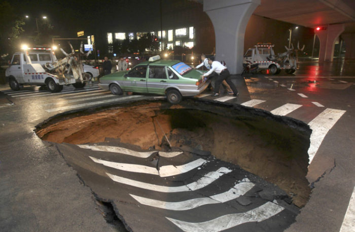 sinkhole, taxi sinkhole, sinkhole swallows taxi, taxi in sinkhole, A taxi stuck in a giant sinkhole in Zhengzhou, Henan province, China, sinkhole, sinkhole china, sinkhole picture, sinkhole photo