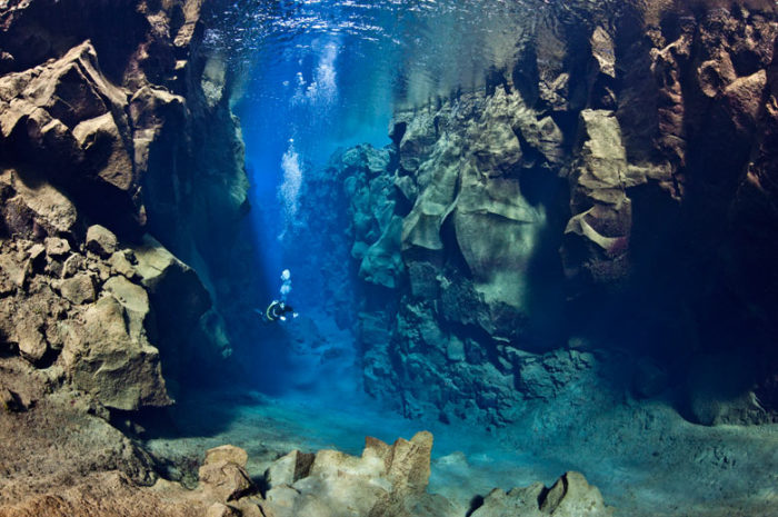 tectonic plate speed, Earth's tectonic plates have doubled their speed, tectonic plate doubled speed, earth tectonic activity, increasing tectonic activity, earth tectonic activity tectonic plate diving, This american diver swims between the eurasian and north american tectonic plates in Silfra Canyon at Thingvellir National Park in Iceland. Photo: Alexander Mustard, earth tectonic, tectonic activity, volcanic eruption, tectonic plates speed
