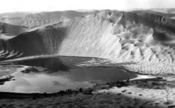 lake and megadune at Badain Jaran Desert, lake desert, lake desert china, geological oddity: megadune and desert lake Badain Jaran Desert, desert lake Badain Jaran Desert, Badain Jaran Desert megadune, An eight-meter deep lake with an area of one km2 in the Badain Jaran Desert, ca 300 m-high dunes in the back.