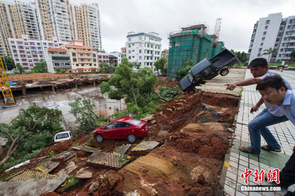 A giant sinkhole has swallowed up a parking lot in Haikou China, parking collapse haikou china landslide, landslide haikou china, sinkhole swallows parking lot china haikou, A man looks on as cars are seen stuck in a sinkhole that occurred in a parking area after heavy rainfall hit Haikou, A giant sinkhole has swallowed up a parking lot in Haikou, China. Photo: Reuter