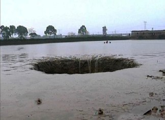 sinkhole swallows pond china, sinkhole drains out pond china, sinkhole drains pond and swallows up 25 tons of fish, fish swallowed by sinkhole in china, china sinkhole swallows pond and fish