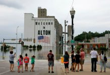 People gather in downtown Alton, Ill. on Saturday as the Mississippi River there reached a level of 39 feet. The red line under the American flag painted on the grain silos represents the high-water mark of 42.72 feet, recorded in 1993. (David Carson/St. Louis Post-Dispatch via AP)