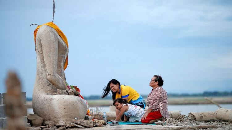 Thailand underwater temple reemerges drought, Thailand underwater temple reemerges drought august 2019, Thailand underwater temple reemerges drought video, family praying near the ruins of a headless Buddha statue that resurfaced in a dried-up dam because of a drought in Lopburi, Thailand, on Aug. 1, 2019